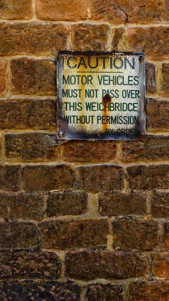 Vintage weighbridge sign on stone wall